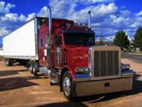 An image of a large factor trailer with a red bag and white container in the rear.